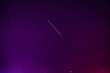 Meteoric Track In Violet Night Starry Sky Background. Glowing Stars