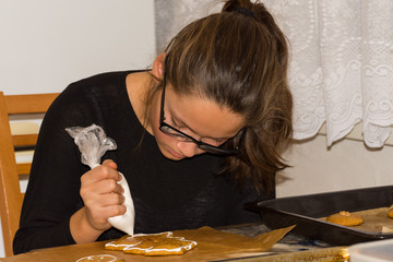 girl decorates gingerbread with white cream