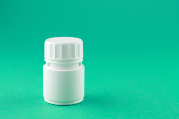 Close up white pill bottle on emerald green background with copy space. Focus on foreground, soft bokeh. Pharmacy drugstore concept