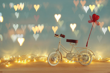 Valentine's day romantic background with white vintage bicycle toy and glitter red heart on it over wooden table.