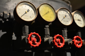 A lot of ball valves, arranged in a row. Cranes have red knobs. Detail of the heating system.