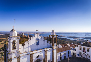 Aerial view of a church facade in the historic village of Monsaraz in Alentejo with the Alqueva dam reservoir on the background; Concept for travel in Portugal and most beautiful places in Portugal