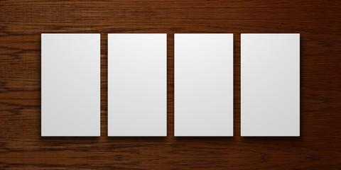 vier leere weiße Leinwände vor einem dunklen Holzhintergrund