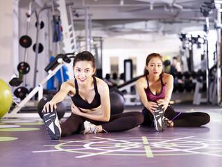 beautiful young asian women stretching legs in gym