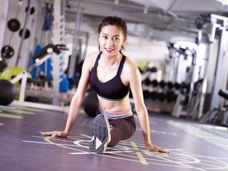 beautiful young asian woman stretching legs in gym