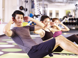 group of young asian people exercising in gym