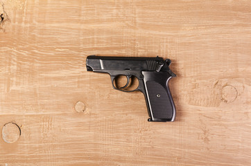 Weapon. Pistol on wooden background. Firearms for protection and secure.