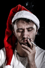 Unshaven man in a Christmas hat smoking a cigarette