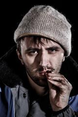 Unshaven man smoking a cigarette