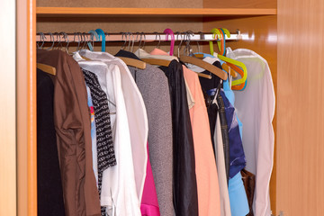 Hangers with clothes inside wardrobe