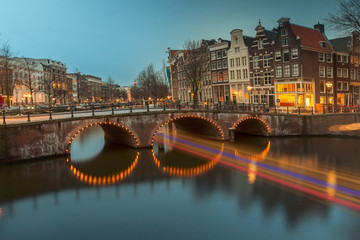 Iconic Amsterdam view with its canals and illuminated boats sailing across and under the narrow bridges pathway, Netherlands