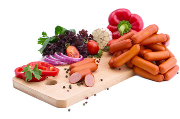 Fresh sausages, lettuce, red pepper and tomatoes on a wooden board. Meat composition on a white background.