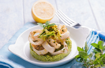 rings squid with  and grated lemon over zucchinis cream