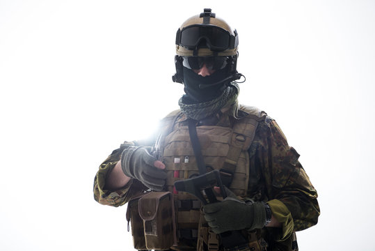 Portrait of serene defender holding assault rifle while looking at camera. Army concept. Isolated