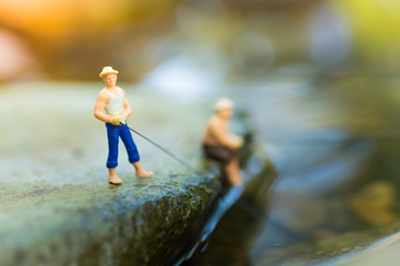 Miniature fisherman sitting on stone, fishing in the river. Macro view photo, use as a fishing career concept.