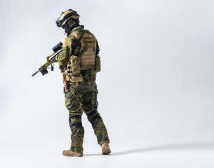 Full length side view serene defender in army clothes keeping assault rifle. Protection concept. Copy space