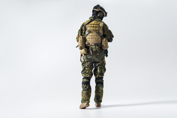 Full length soldier facing away while wearing protective military uniform. Maintenance concept