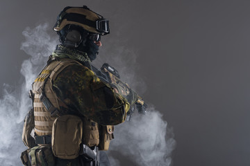 Side view orderly soldier in balaclava and helmet keeping assault carbine in arms. He standing in smoke. Army concept. Copy space
