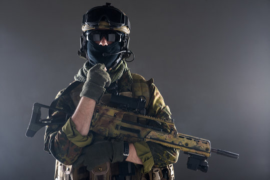 Portrait of serene soldier in generic military uniform keeping assault rifle in arm. Protection concept. isolated