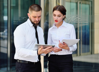 business man and business woman in office business style talking and looking at the tablet on the background of an office building