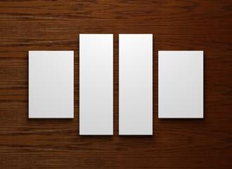 vier leere weiße Bilderrahmen auf einem Holzhintergrund