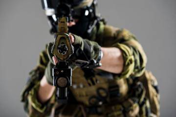 Close up soldier arms holding weapon with collimator sight while wearing modern ammunition. Protection concept. Selective focus
