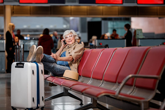 Talk with friends. Full length portrait of aged woman is sitting on bench at waiting hall while putting feet on suitcase. She is having pleasant conversation on mobile phone. Copy space in right side