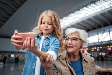 For long memory. Portrait of positive little girl is taking selfie with her elegant grandmother using mobile phone. They are posing at international airport while waiting for boarding