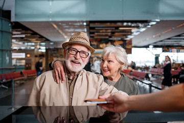 Have nice trip. Portrait of cheerful gray-haired couple is standing at international airport near registration desk. Old man is taking his tickets while aged woman is looking at him with love