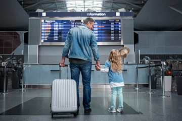 Wall Mural - Lets find our flight. Full length back view of happy father is standing hand by hand with little daughter in terminal against electronic board. He is looking at her with smile while holding suitcase