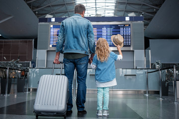 Wall Mural - Lets travel abroad. Full length back view of stylish father is standing hand by hand with his little daughter in airport. They are looking at electronic timetable while man is holding suitcase