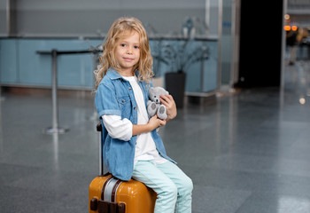 Travel time. Portrait of cheerful blonde pretty girl is sitting on suitcase at international airport with her favorite toy. She is looking at camera with slight smile. Copy space in the right side