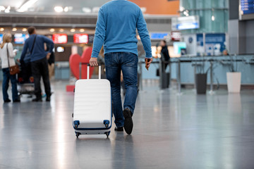 Always on move. Back view of confident man in casual clothes is walking along airport lounge while carrying his baggage. People in background