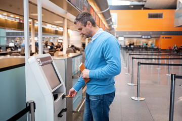 Side view profile of serious mature man is standing near self-service check-in kiosk at international airport building. He is using his credit card to making payment for flight tickets