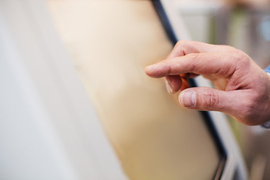 Verify orders. Close-up of fingers of man is touching display of self-service kiosk. Copy space in the left side