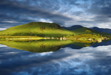 Perfect still reflection loch at sunrise Rannoch Moor Glencoe Scottish highlands