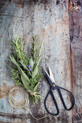 Bouquet Garni Herbs with String and Scissors on Grunge Timber Background