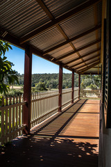 Outdoor verandah patio deck of sandstone brick cottage with picket fence in sunshine with trees in background