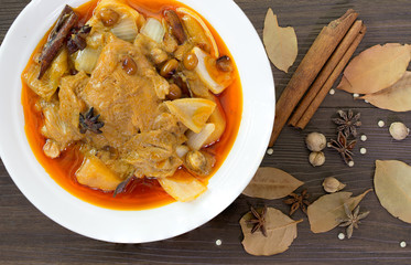 Massaman curry chicken in white bowl and ingredients herb all on brown background