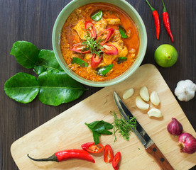 Chicken panang curry in the white bowl and fresh spice on brown wooden background Thai food