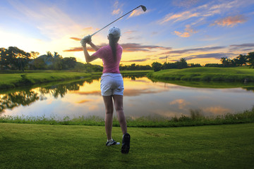 a woman golf player in an action of ene of downswing after hit the golf ball away from tee off to the fairway ahead by iron driver
