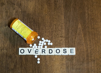 Tan tiles with black capital letters spelling Overdose with an open prescription bottle and white oxycodone tablets spilling out onto a wood table.