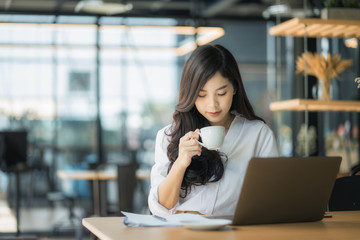 Young business woman using on the laptop while sitting at her working place.