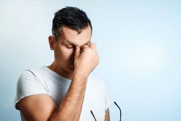 Close-up portrait of a man, covering his face with his hands. On a light background. The concept of body language.