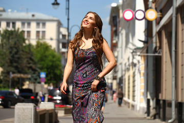 Beautiful young woman in long colorful dress