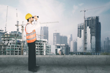 Architect looking at the construction site with binocular