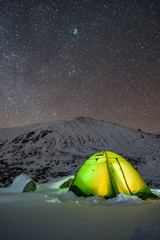 Glowing in the dark tent at Musala, Rila mountain, Bulgaria - frosty night under the starry winter sky - amazing advanture