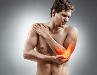 Young man holding his inflamed elbow. Medical concept