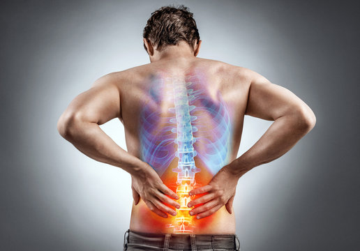 Lower back pain. Man holding his back in pain. Medical concept.