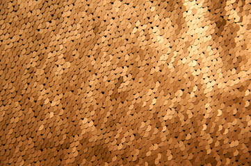Texture of gold sequins close-up macro abstract shiny background. Fashionable expensive fabric with sequins.